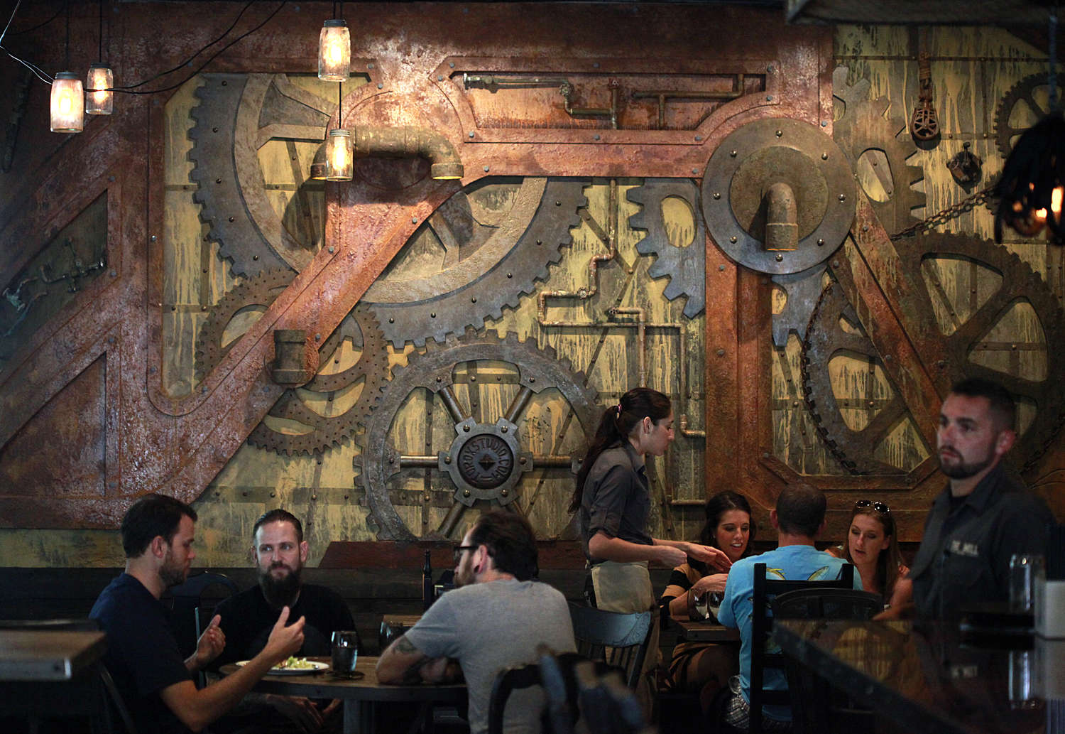 Diners at tables in front of a wall decorated with industrial gears and pipes
